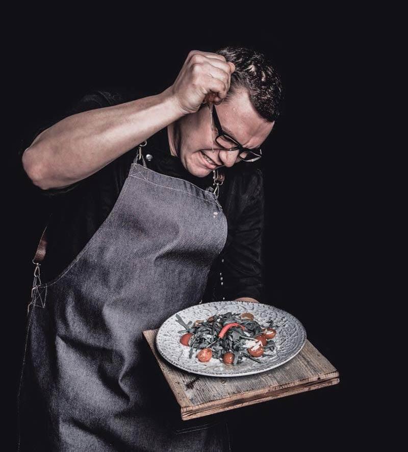 Mann mit Denimschürze mit Lederträgern welcher Salatdressing verfeinert