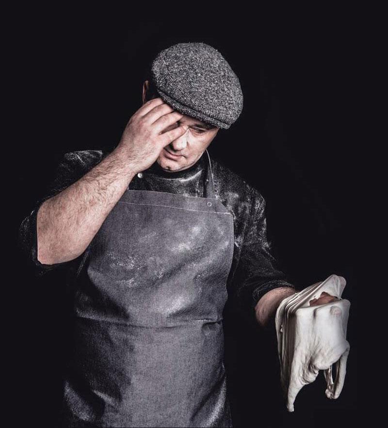 Mann mit Denimschürze mit Gewebeträgern welcher Teig zubereitet