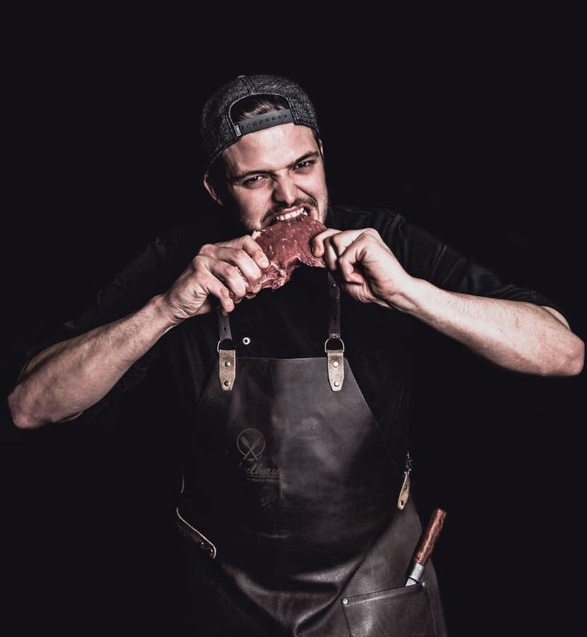Mann mit schwarzer Lederschürze welcher in rohes Steak beißt